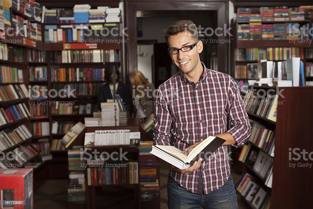 young attractive guy in a bookstore stock photo