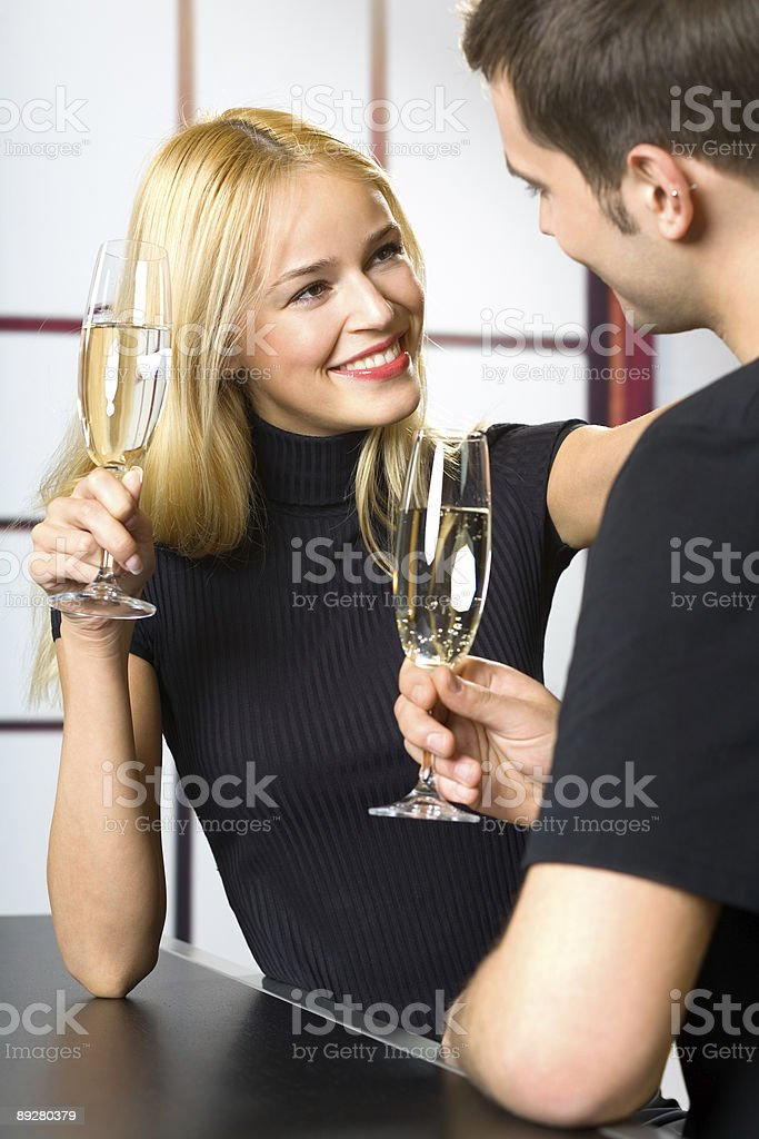 Young attractive happy smiling couple celebrating with champagne, indoors royalty-free stock photo