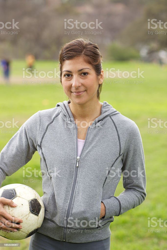Young attractive Hispanic woman with soccer ball stock photo