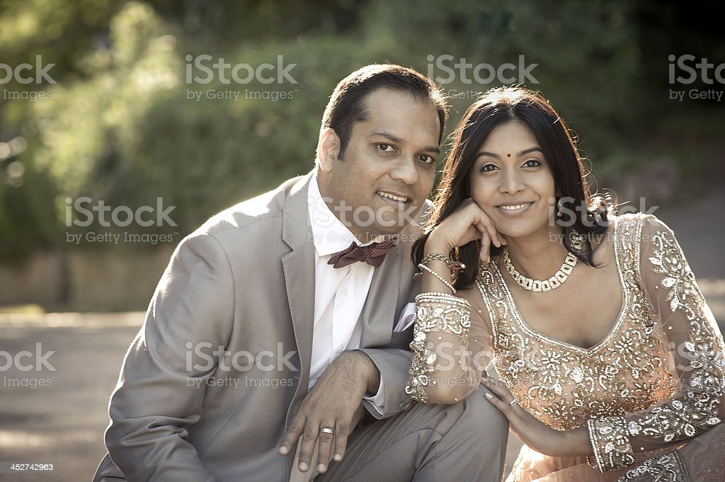 Young attractive indian couple sitting together in formal wear stock photo