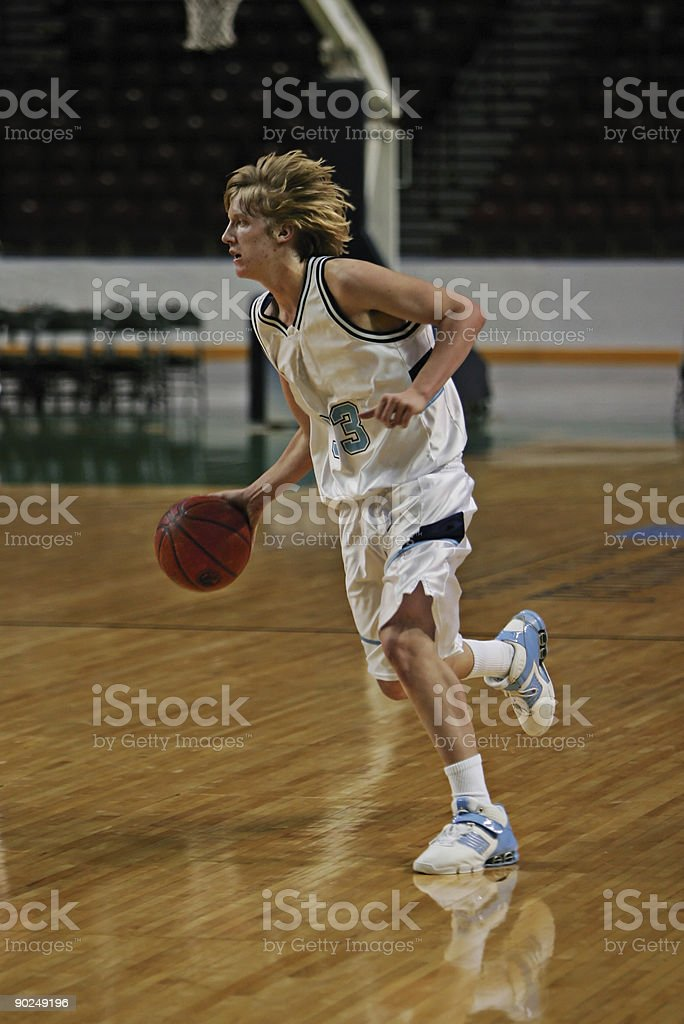 Young, Attractive Male Basketball Player Dribbles Down Court stock photo