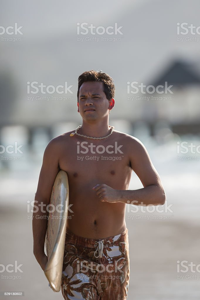 Young attractive male surfer running on the beach stock photo