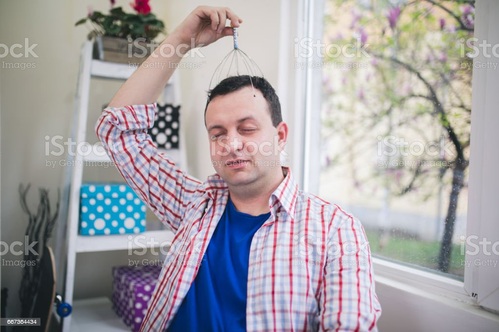 Young attractive man at modern office desk, massaging temples to forget about constant headaches stock photo