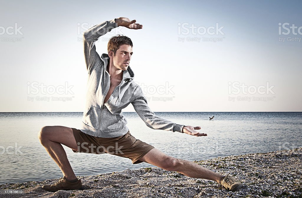 A young, attractive man doing Thai-Chi on a beach stock photo