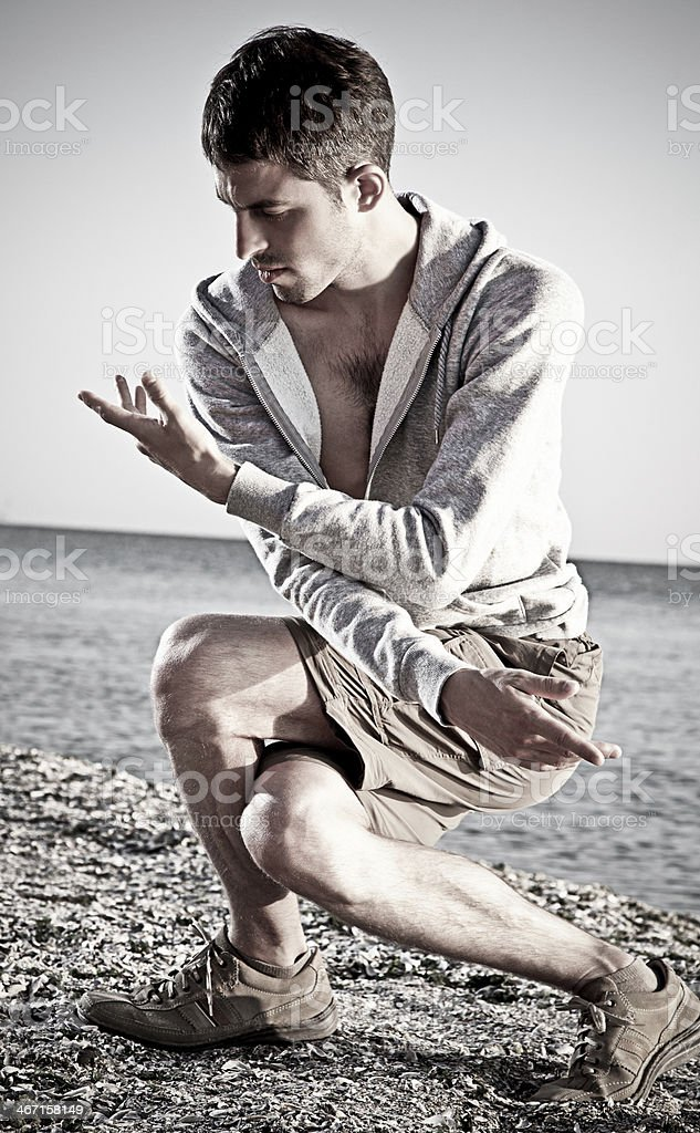 Young attractive man making Thai-chi movements on the beach royalty-free stock photo