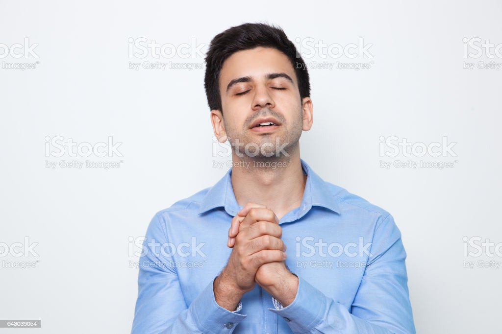 Young Attractive Man Praying With Clasped Hands stock photo