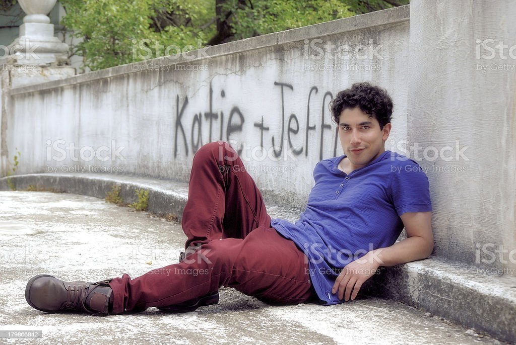 young attractive man reclining against stone wall royalty-free stock photo