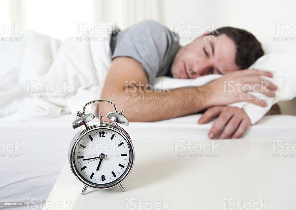Young attractive man sleeping on bed stock photo