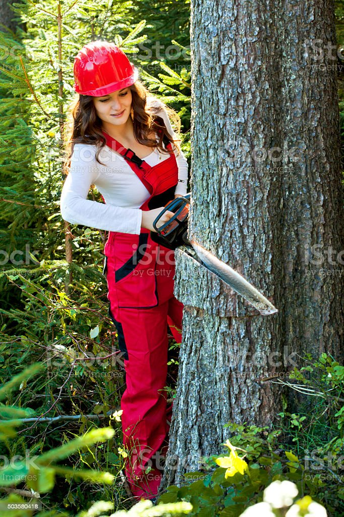 Young attractive woman as lumberjack with chainsaw stock photo