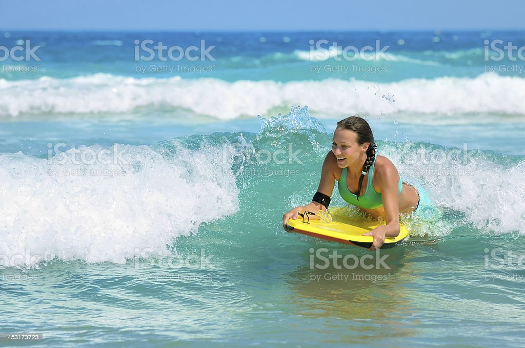 Young attractive woman bodyboards on surfboard with nice smile stock photo