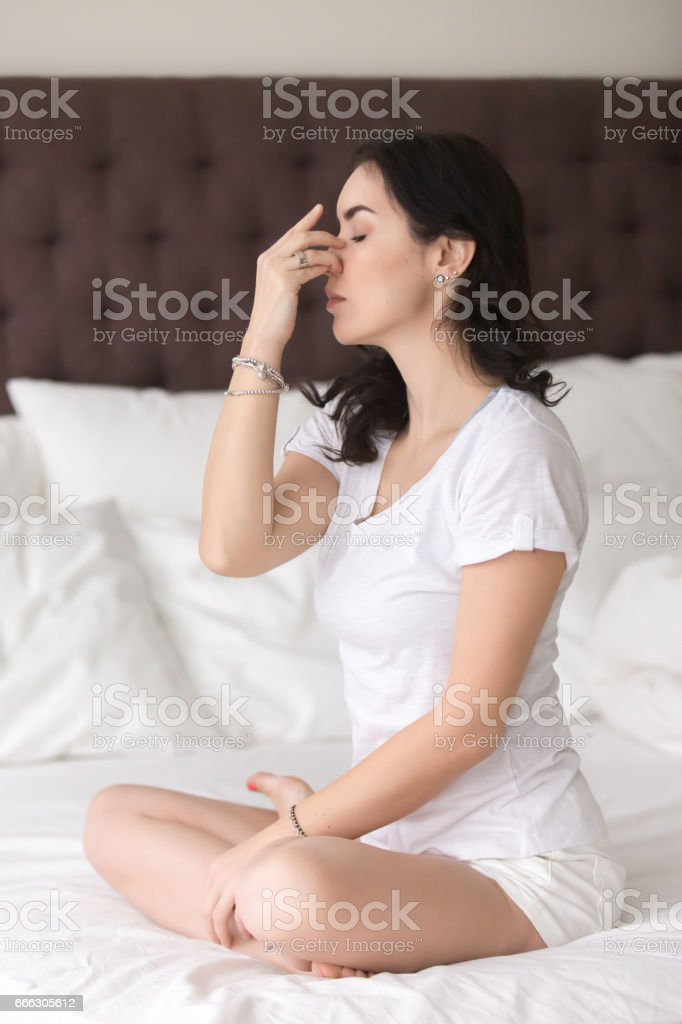 Young attractive woman doing Alternate Nostril Breathing pose on bed stock photo
