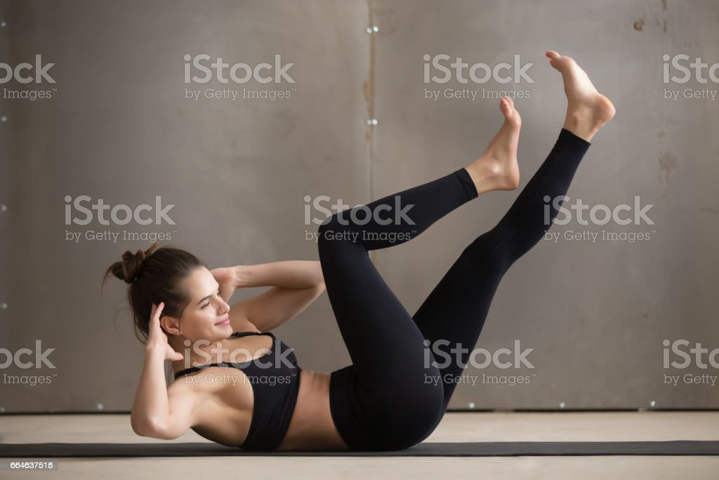 Young attractive woman doing bicycle crunches, grey studio backg stock photo