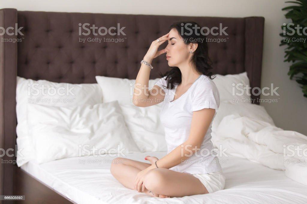Young attractive woman doing nadi shodhana pranayama pose on bed stock photo