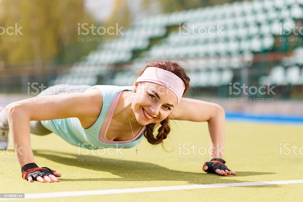 Young attractive woman doing push-up or core stock photo