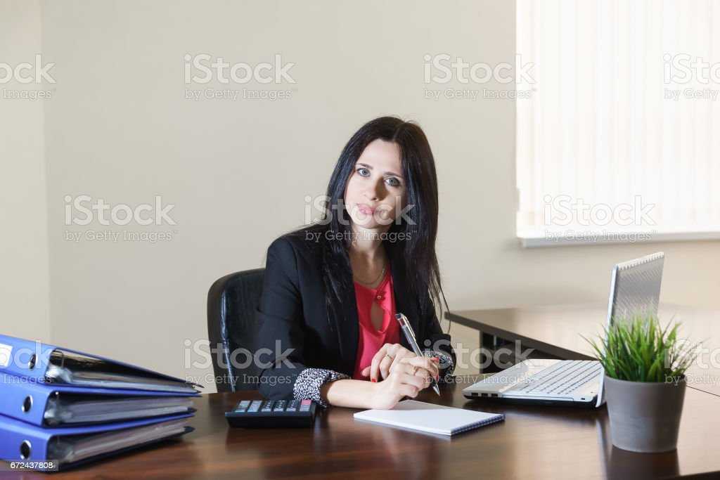 Young attractive woman in a business suit taking notes in Notepad at Desk in office stock photo