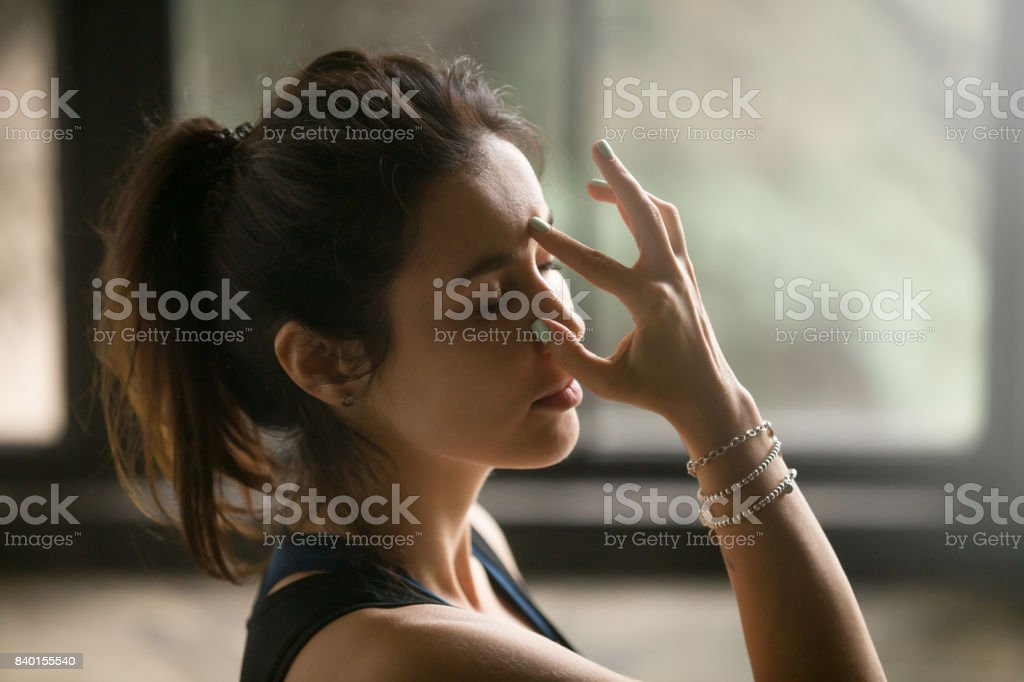 Young attractive woman in Alternate Nostril Breathing, studio background stock photo
