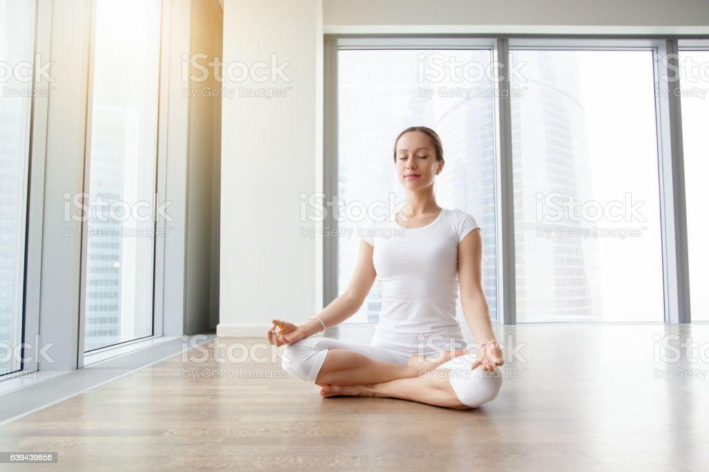 Young attractive woman in Ardha Padmasana pose against floor win stock photo