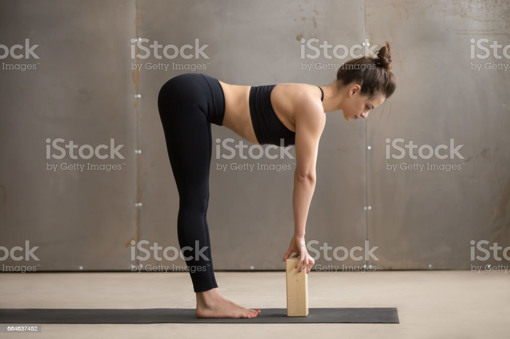 Young attractive woman in Ardha uttanasana pose with block, stud stock photo