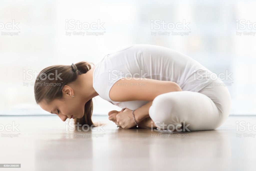 Young attractive woman in baddha konasana pose against floor win stock photo
