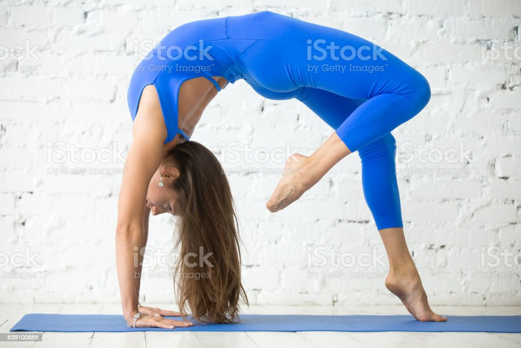 Young attractive woman in Bridge pose, white studio background stock photo