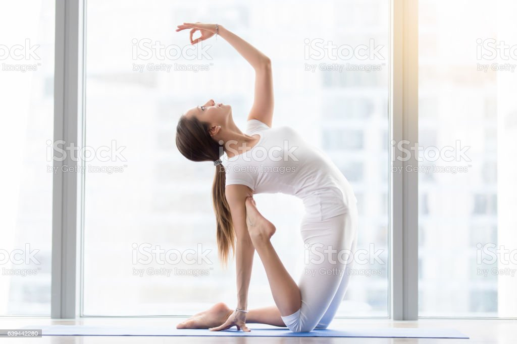 Young attractive woman in Camel pose with mudra, floor window stock photo