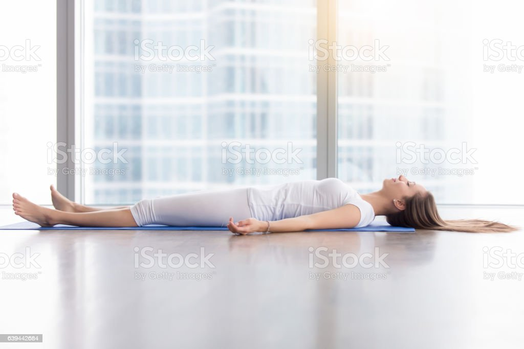 Young attractive woman in Corpse pose against floor window stock photo