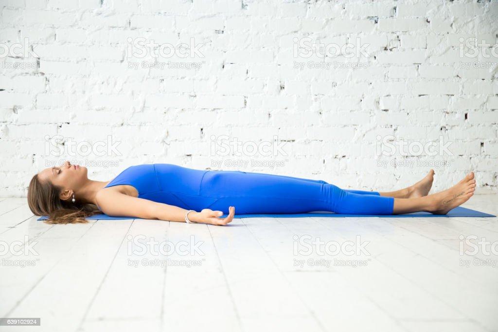 Young attractive woman in Dead body pose, white studio backgroun stock photo