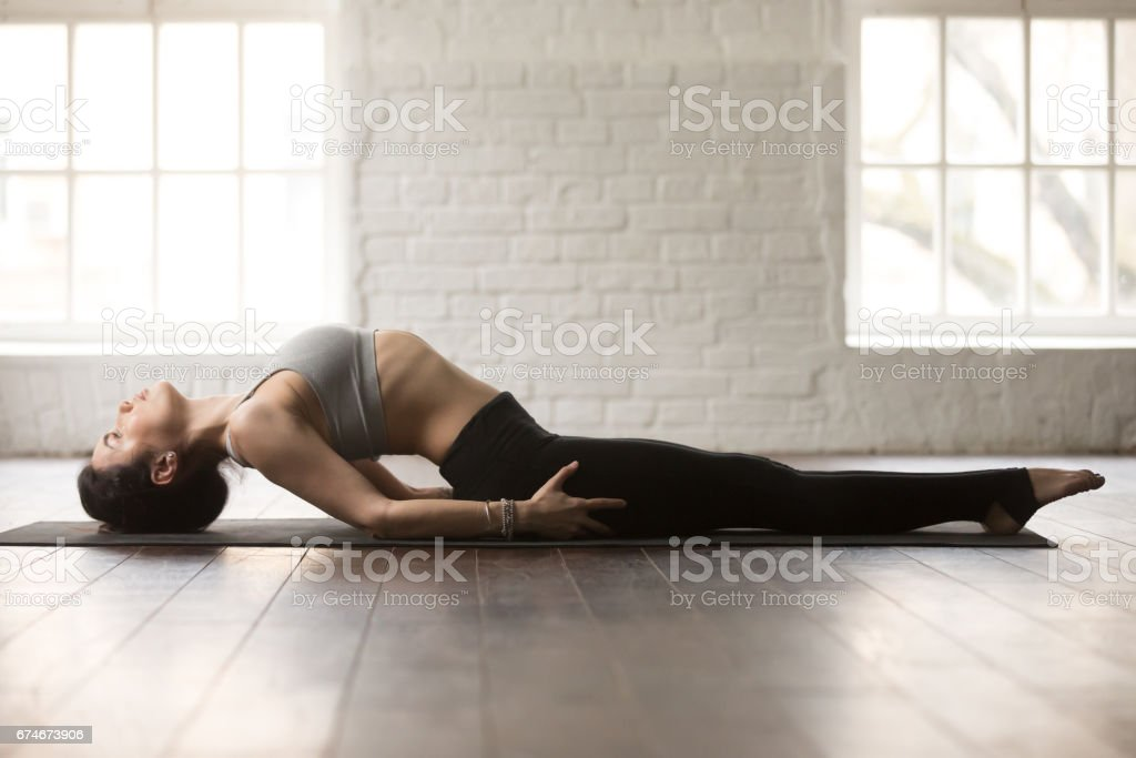 Young attractive woman in Fish pose, white loft studio backgroun stock photo