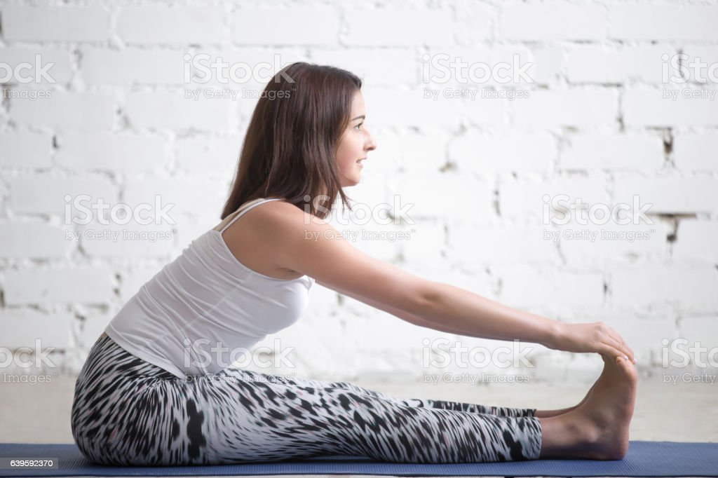 Young attractive woman in paschimottanasana pose, white studio stock photo