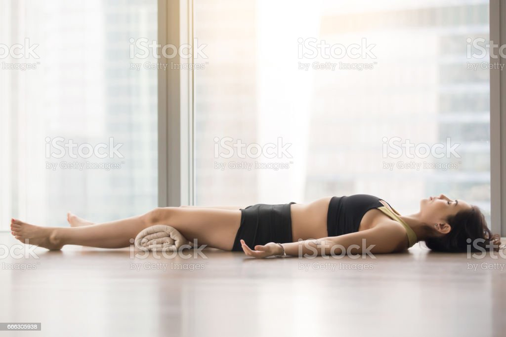 Young attractive woman in Savasana pose against floor window stock photo