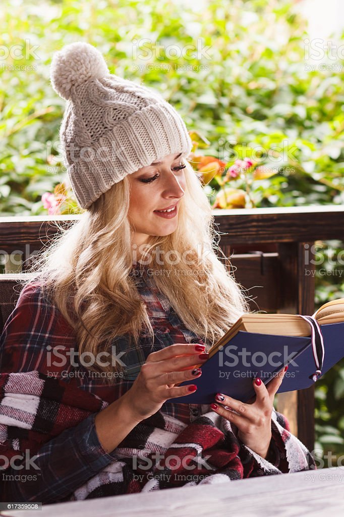 Young attractive woman in the cafe with a book stock photo