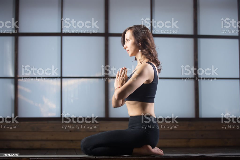 Young attractive woman in the vajrasana pose, studio evening pra stock photo