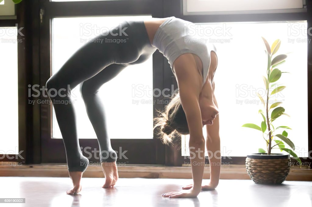 Young attractive woman in Urdhva Dhanurasana pose, home interior stock photo