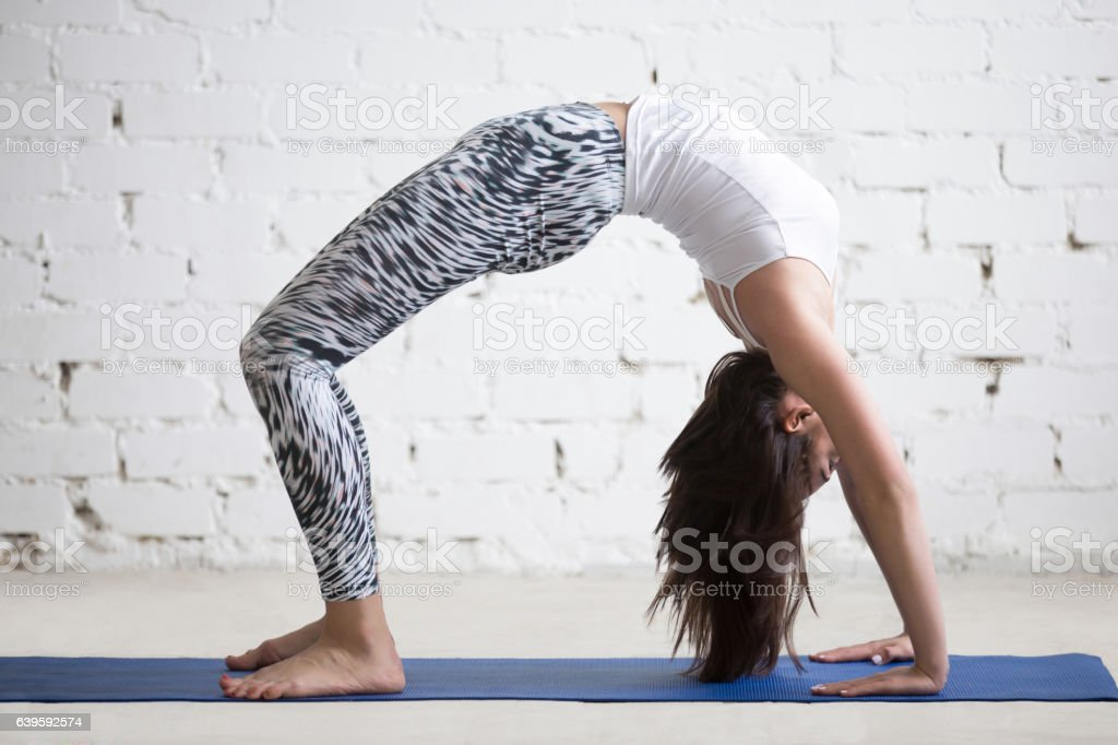 Young attractive woman in Urdhva Dhanurasana pose, white studio stock photo