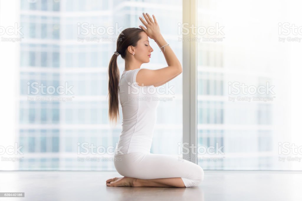 Young attractive woman in vajrasana pose against floor window stock photo