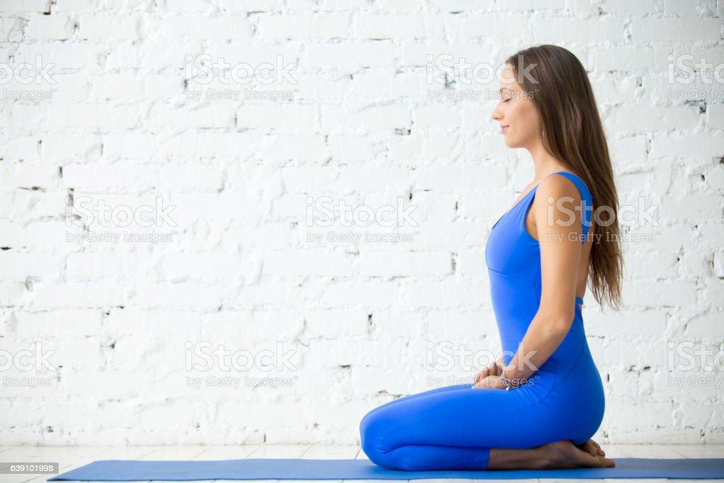 Young attractive woman in vajrasana pose, white studio backgroun stock photo