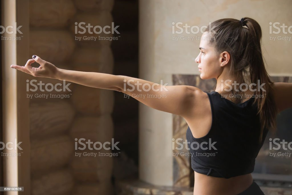 Young attractive woman in Warrior two pose, home interior backgr stock photo