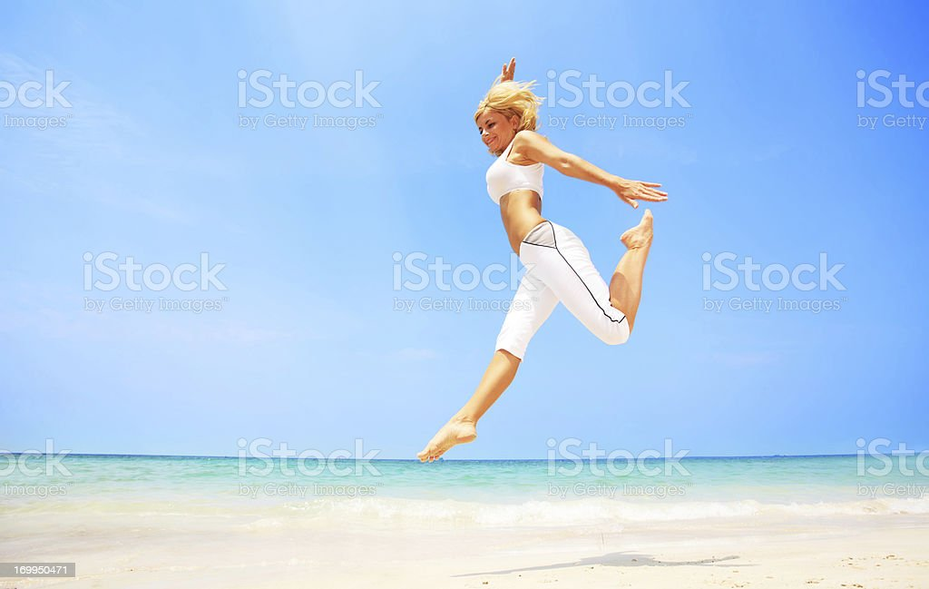 Young attractive woman jumping on the beach. royalty-free stock photo