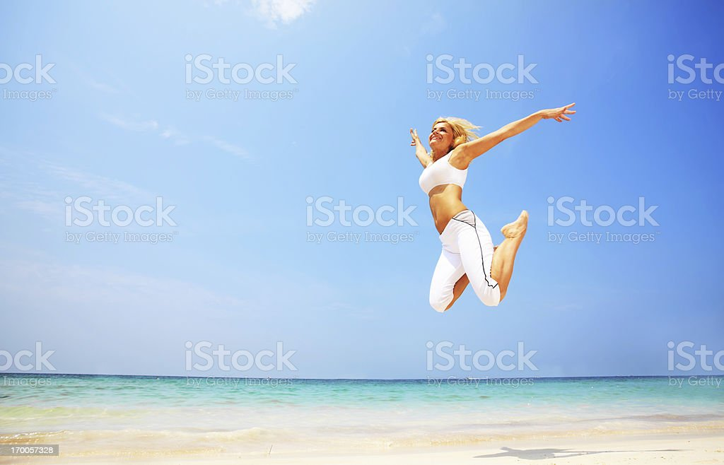 Young attractive woman jumping on the beach royalty-free stock photo
