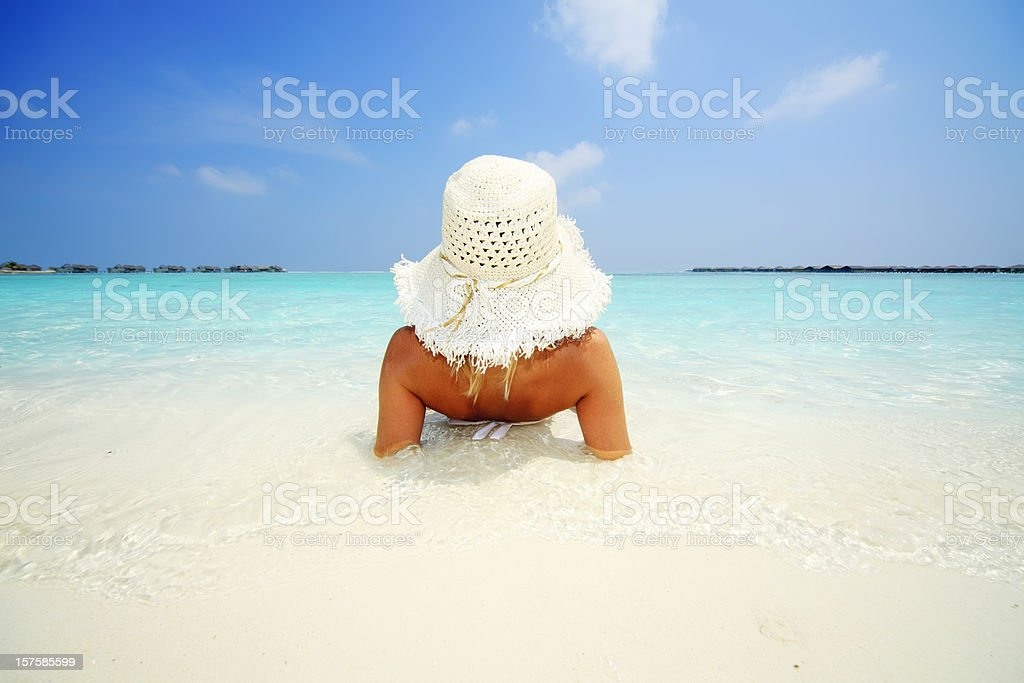 Young attractive woman lying down at tropical sea shore. royalty-free stock photo