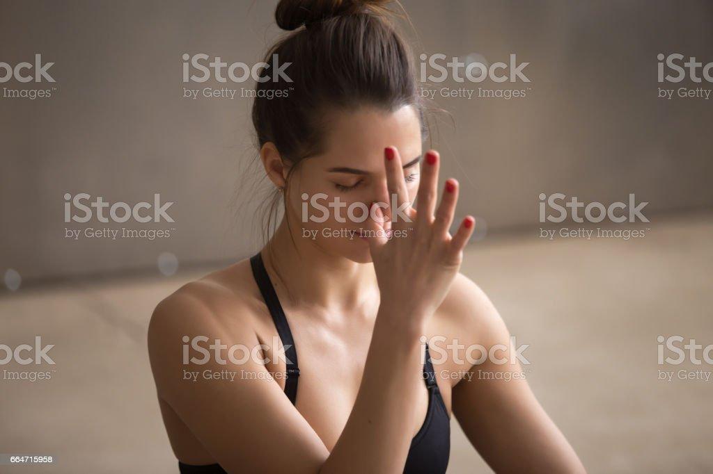 Young attractive woman making nadi shodhana pranayama, grey stud stock photo