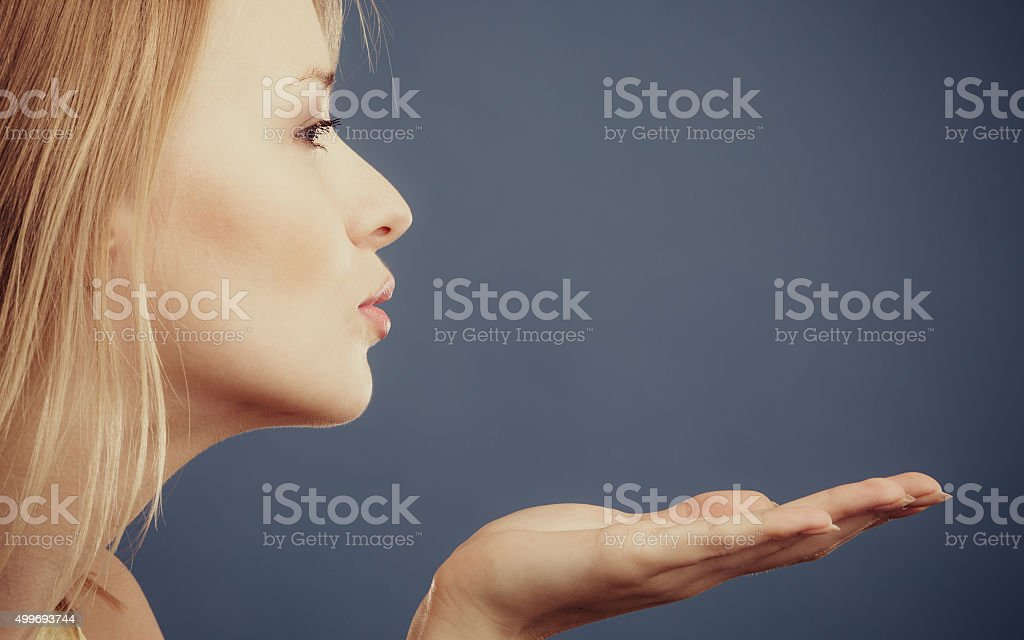 Young attractive woman sending hand kiss. stock photo