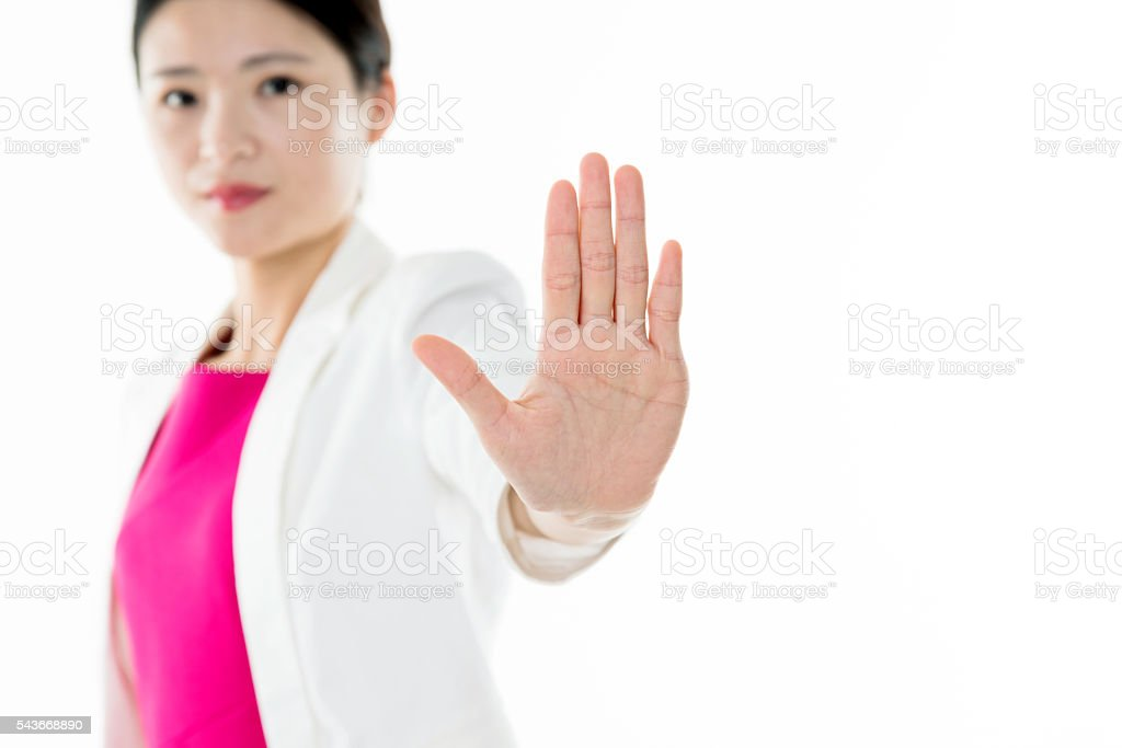 Young attractive woman show STOP against white background stock photo