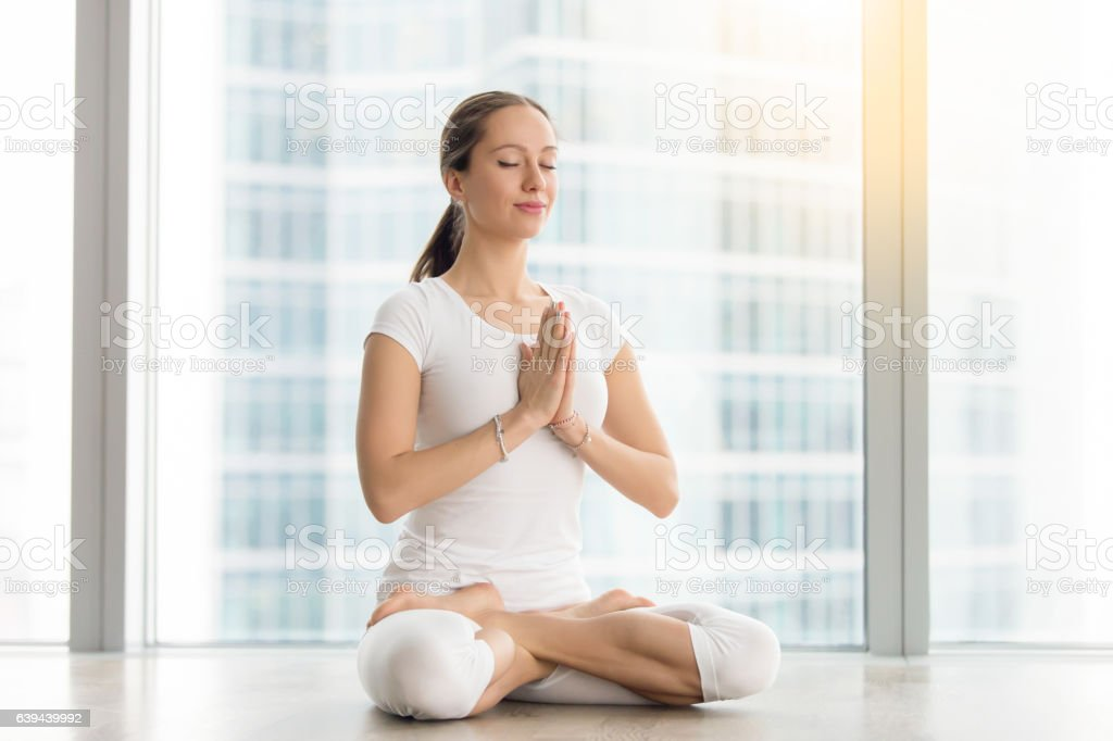 Young attractive woman sitting in Padmasana pose against floor stock photo