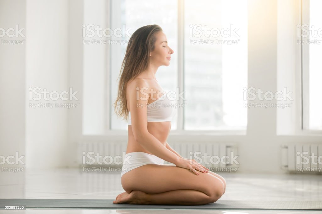 Young attractive woman sitting in vajrasana pose, white color ba stock photo