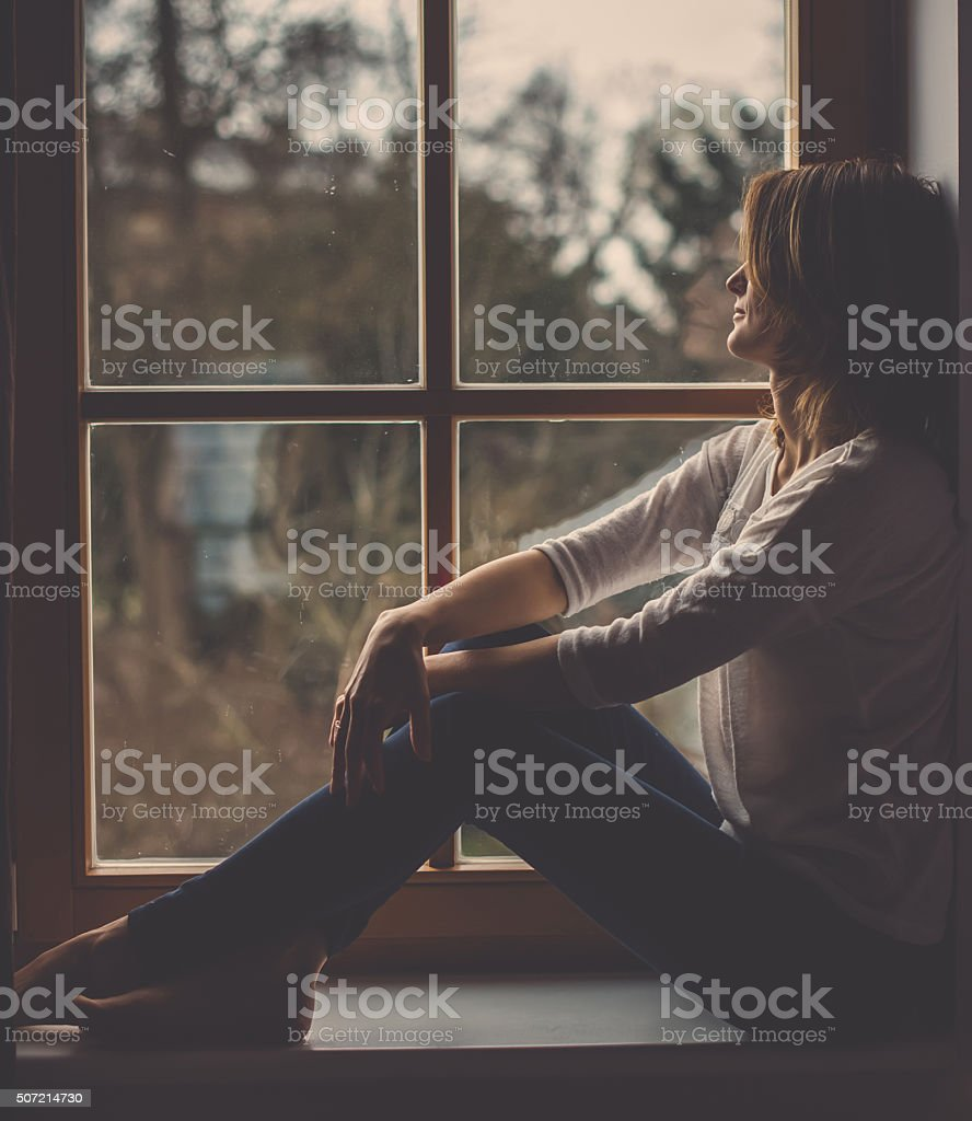 Young attractive woman, sitting on a window, looking outside stock photo