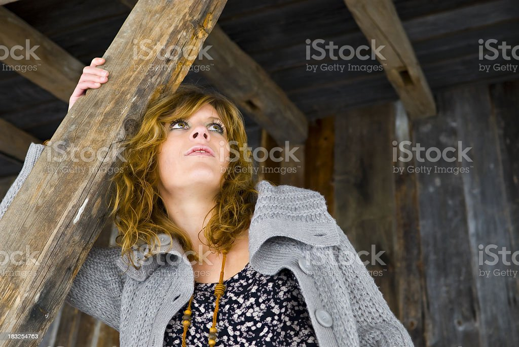 young attractive woman sitting on wood and looking in sky royalty-free stock photo