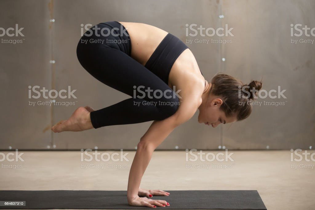 Young attractive woman standing in Bakasana pose, grey studio ba stock photo
