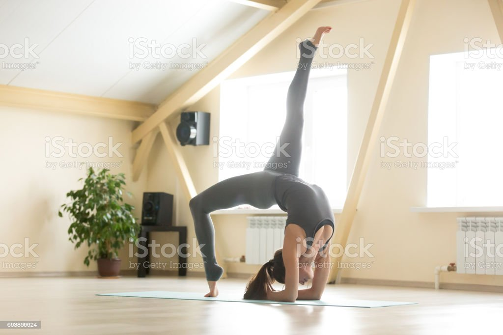 Young attractive woman standing in Elbow Bridge pose, home inter stock photo