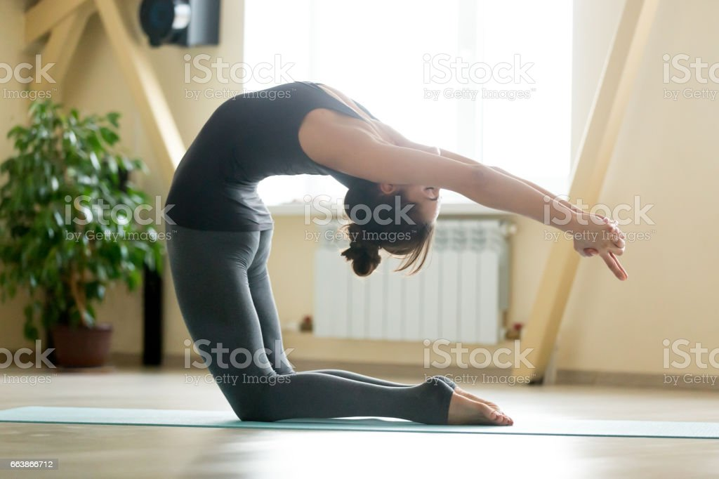 Young attractive woman stretching in Camel pose, home interior b stock photo